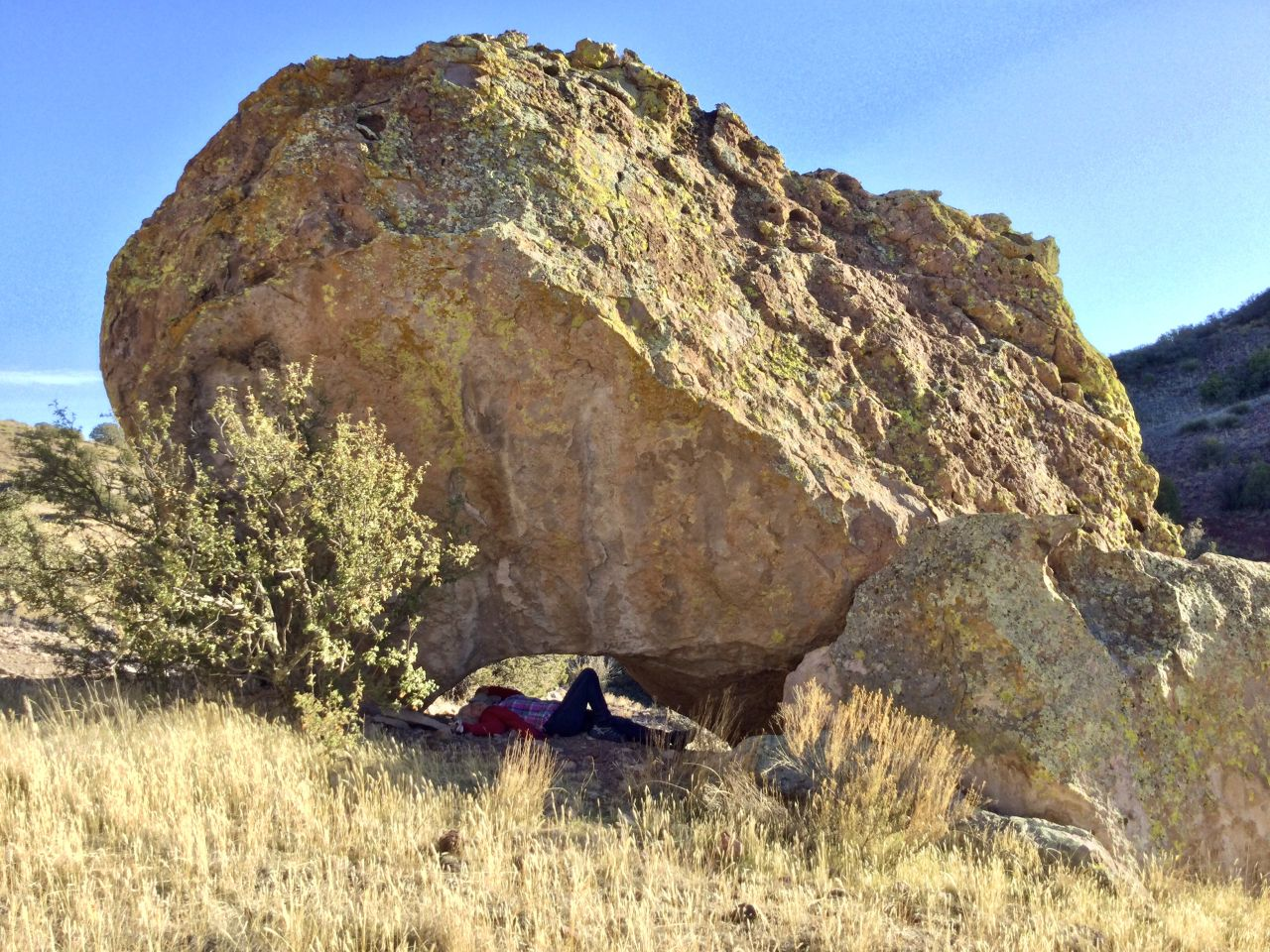 hiker reclining under rock arch